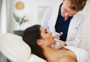 Young male doctor doing botox injections on a woman's lips