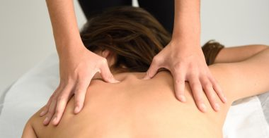 Young woman receiving a back massage in a spa center. Female patient is receiving treatment by professional therapist.